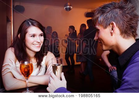 young couple is flirting in a nightclub