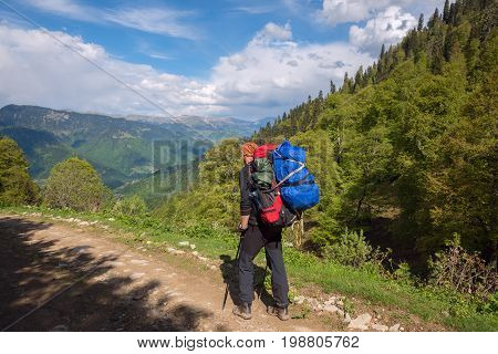 Man Adventurer With Big Backpack Goes Along The Mountain Road