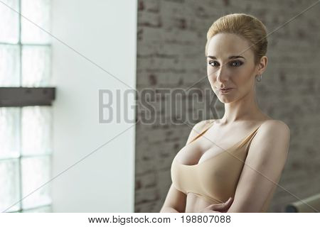 Slender Blonde Girl Ballerina In Bright Dancing Hall. Woman With Big Breast And In Beige Underwear
