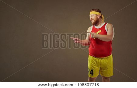 Thick funny freak man in sports clothes points with his finger.
