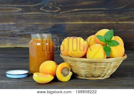 Apricot jam and fresh apricots in the bowl on wooden table