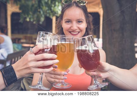Female toasting and cheering aperitif beers half pint with her friends at restaurant