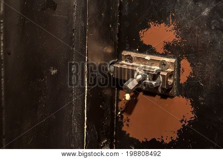 Retro sliding bolt on vintage dark obsolete wooden door