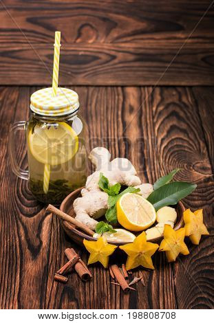 A composition of a mason jar of green tea with a lemon slice and yellow straw on a wooden background. A brown plate with cut lemon, ginger, mint, cinnamon and stars of carambola on a desk.