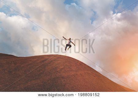 Crazy and brave man athlete jumps on dunes and hills in desert. Deft athlete is engaged in extreme sports on outdoor