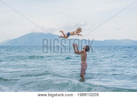 Young Happy Father Holding Up In His Arms Little Son Putting Him Up At The Beach Waves Wet Sand Havi