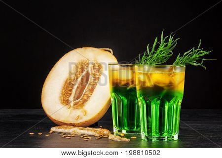 Two beautiful glasses of alcoholic drink with ice, tarragon herbs and melon slices on a black background. Refreshing and fruity alcoholic summer beverages. Fresh melon and cold cocktails. Copy space.