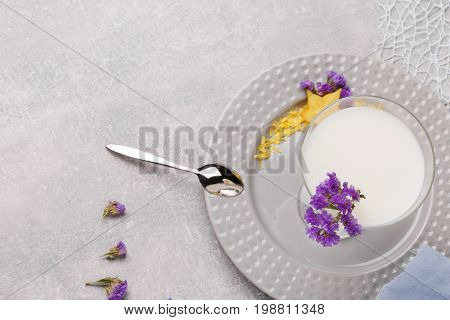 A view from above on a plate with a healthful non-alcoholic smoothie, purple flowers and a spoon on a white background. Vegetarian homemade desserts with milk and fruits. Copy space.