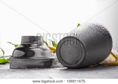 A close-up picture of a cocktail mixer with cool droplets on a gray background. A silver opened shaker on a light gray table. A kitchen tool for making refreshing summer beverages. Copy space.