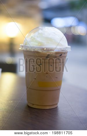 Chocolate frappe with whipped cream in plastic glass on wooden table in a cafe
