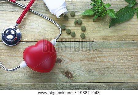 Healthy hearth concept Herbal Medicines with herb leaf and ear doctor on wood background