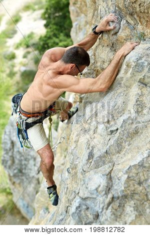 adult man rock climber. rock climber climbs on a rocky wall. man makes hard move