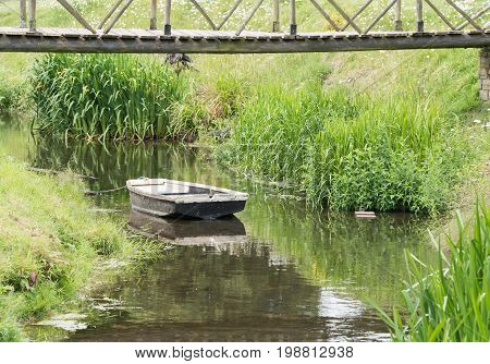 An old wooden rowboat moored in a small stream.