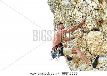 adult man rock climber. rock climber climbs on a rocky wall. man makes hard move