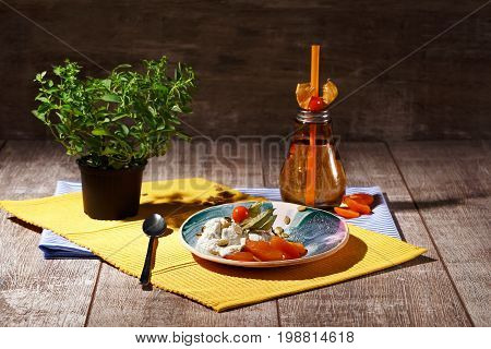 A sweet dessert with dried apricots, physalis and pumpkin seeds on a yellow cloth and on a wooden background. A glass of hot tea with straw near the plate with ice cream. A pot with a green plant.
