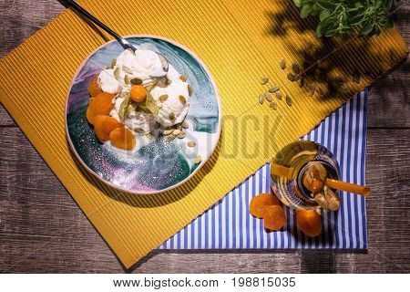 A view from above on a composition of natural summer products. A big bowl of fruity ice cream with apricots, crunchy nuts, a little tree and a bottle of cold drink on a wooden table background.