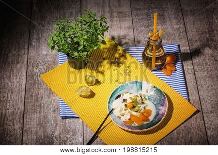 A top view of ice cream with dried apricots, physalis and pumpkin seeds on a yellow fabric and on a wooden background. A glass of green tea with straw near the dessert. A clay pot with a green plant.