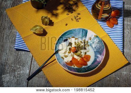 Cold and tasty vanilla ice cream with physalis, pumpkin seeds, and dried apricots on a yellow fabric and on a wooden background. A little tea spoon near the dessert. A beverage on a striped cloth, top view.