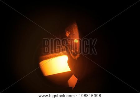 Hard work in the aluminum foundry. Steel factory. Orange molten steel. Melting furnace on a black background.  Metallurgical business. Production of steel. Copy space.