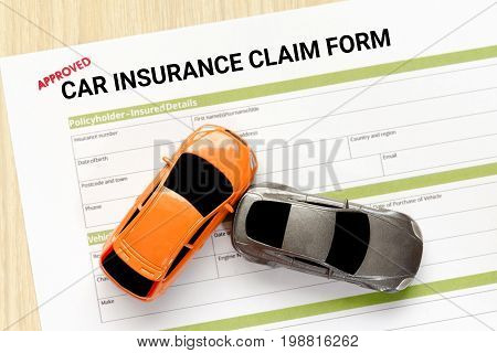 Top view of approved car insurance claim form with accident car toy on wooden desk - accident concept