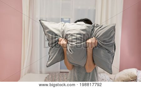 Depressed Woman Covering Her Face With Pillow And Screaming In Anger In Her Room