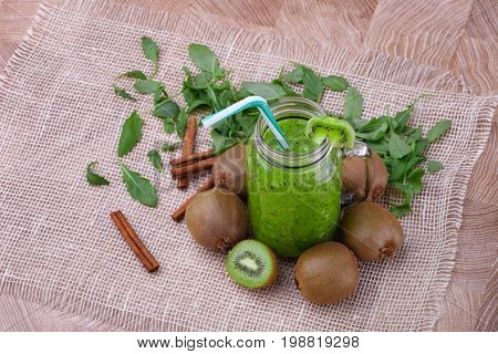 A top view of a healthy kiwi smoothie in a mason jar with a colorful straw and slice of fruit on a top on a wooden background. Exotic whole and cut kiwi, cinnamon sticks and leaves on a white cloth.