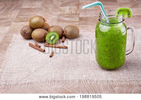 A big mason jar full of organic beverage from ripe kiwi with a colorful straw and slice of fruit on a top on a wooden background. A heap of whole and cut kiwi and cinnamon on a light tablecloth.