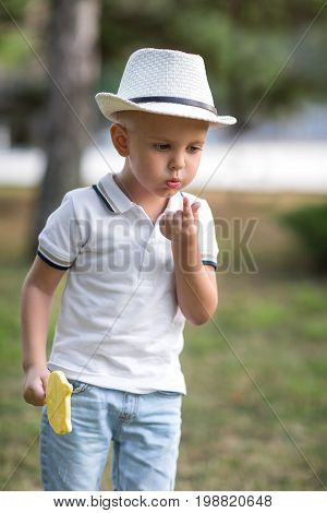 A curious little kid in a fancy hat blowing on his finger. A stylish boy with a lemon candy walking on a light garden background. A portrait of a thoughtful and concerned child.