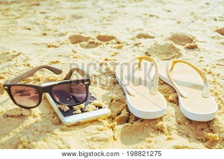 sunglasses, mobile and flip-flpo on sand beach in sunny day