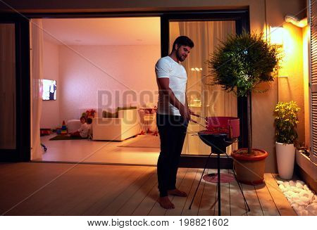 young adult man preparing food for family on evening patio at home