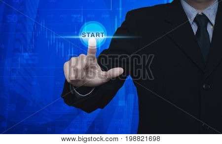 Businessman pressing start button over graph and chart with modern office city tower blue tone Start up business concept Elements of this image furnished by NASA