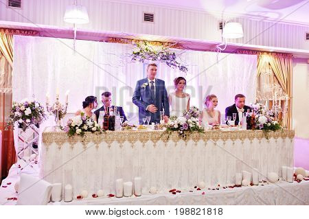 Beautiful Wedding Couple Standing At Their Table With Bridesmaids And Groomsmen Sitting Beside Them.
