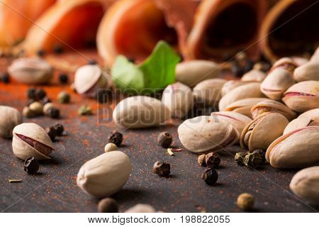 A close-up picture of nutritious pistachios with black and red pepper, fresh spinach and sliced meat on a black background. Pub appetizers and snacks. Nuts full of nutrients.