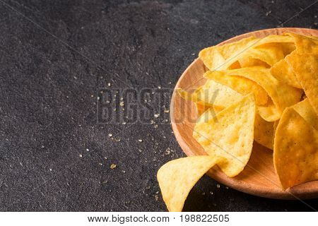 A view from above on gold nacho chips on a light wooden plate. Tasty spicy snacks for alcoholic drinks. Mexican traditional appetizer on a saturated black stone background. Copy space.