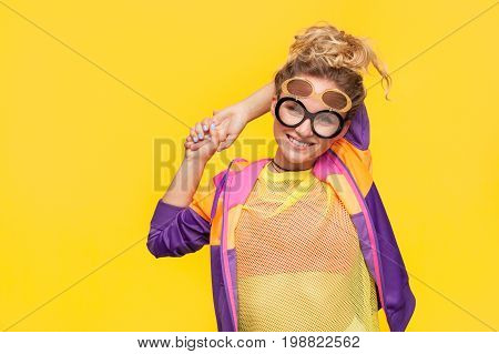 Young woman wearing bright hipster clothing and creative sunglasses looking at camera on orange background.