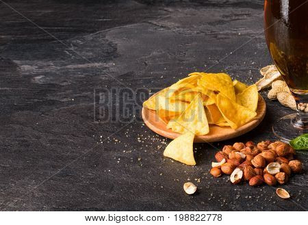 An alcoholic beverage and snacks on a black table background. A plate of classic nachos and brown nuts next to a refreshing beer or ale. Pub, bar and party concept. Copy space.