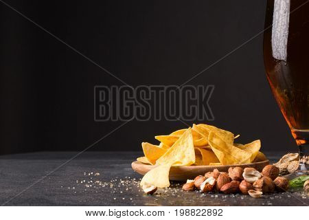 An alcoholic drink and tasty snacks on a stone table background. A plate of yellow hot nachos and pile of nutritious nuts next to a glass of fresh golden beer. Copy space.