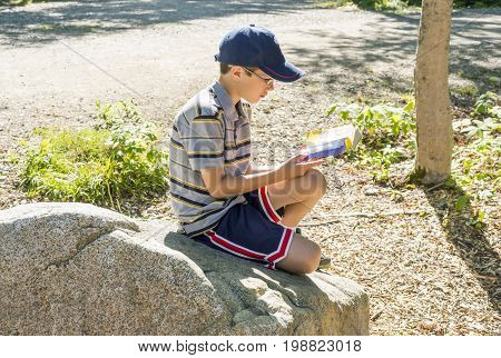 Tween boy reading a book outdoors at camp sitting on a large rock sun shining down. Hat and glasses. Summer reading and outdoor relaxation concept