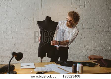 Stylish dressmaker with mannequin creating new clothes in atelier.