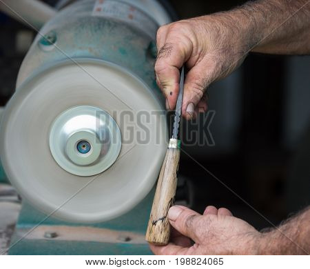 The hands of the craftsman carefully holds a custom made knife against the buffing wheel to carefully polish the finish of the handle.
