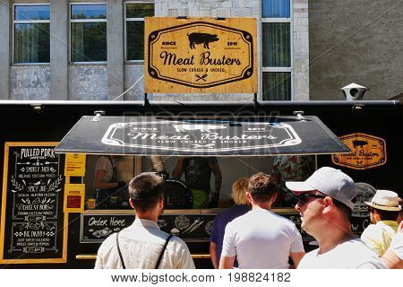 CLUJ-NAPOCA ROMANIA - JULY 9 2017: People buy tasty fast food at a food truck serving pulled pork and other tasty goodies listed on the menu.