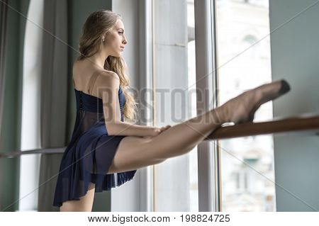 Gorgeous ballerina is training in the ballet hall. She holds her right leg and hand on the ballet barre. Girl wears a blue dance wear and looks into the window. Closeup. Indoors. Horizontal.