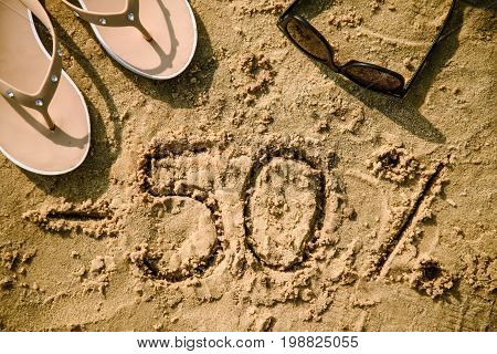 50 lettering written on sand. Summer beach background