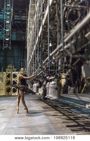 Attractive ballerina stands sideways on pointes next to the big stage light grip in the interior. She wears a black tutu with golden rhinestones and beige ballet shoes. Indoors. Vertical.