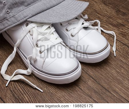 White sneakers with gray cap on dark wooden surface. Sport fashion style for women