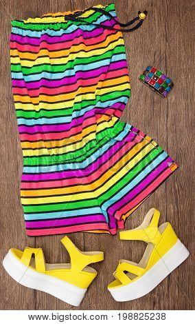 Colorful striped sleeveless romper, yellow wedge sandals and wide multicolored bracelet. Summer fashion. Trendy outfit for women