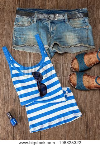 Summer fashion women's outfit in blue tones. Striped tank top of rib knit fabric, denim shorts, comfort sandals with sunglasses and nail polish