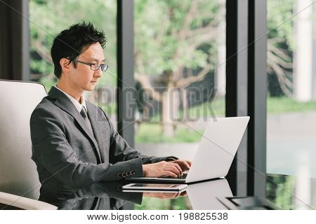 Handsome Asian businessman or entrepreneur at work using laptop computer and digital tablet in executive office. Leadership Business communication startup or information technology gadget concept