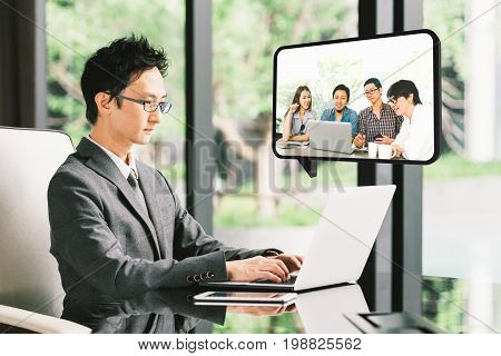 Young Asian businessman CEO entrepreneur VDO conference call with diverse business partner group or employee. Company leader remote live online meeting or financial invest funding advisor concept