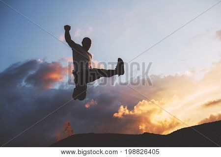 Silhouette of an athlete jumping against background of beautiful clouds at sunset. Athlete jumps. Parkour freerun. Intentional dark colors